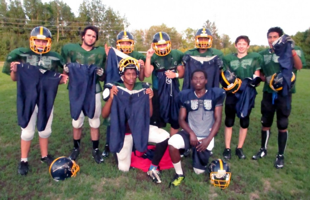 Bell Warrior Bantams holding up the stolen game pants that were anonymously returned 6 days after being stolen.